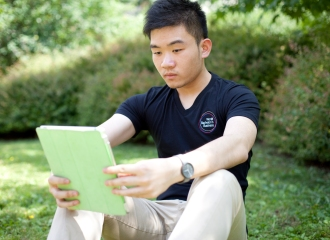 Student in park reading tablet